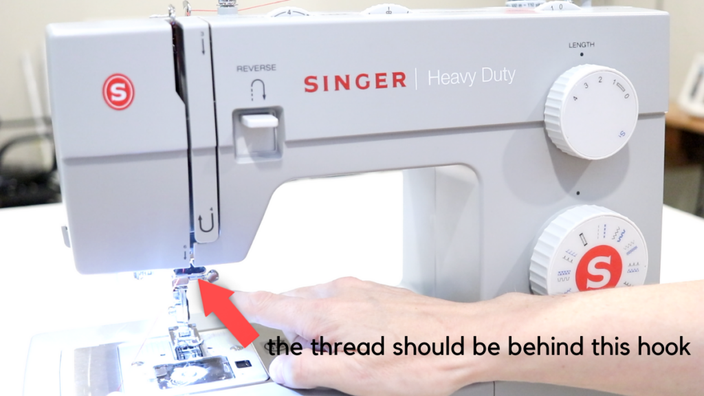 Guide number 6 on a gray singer sewing machine. Red arrow pointing to the guide for the thread
