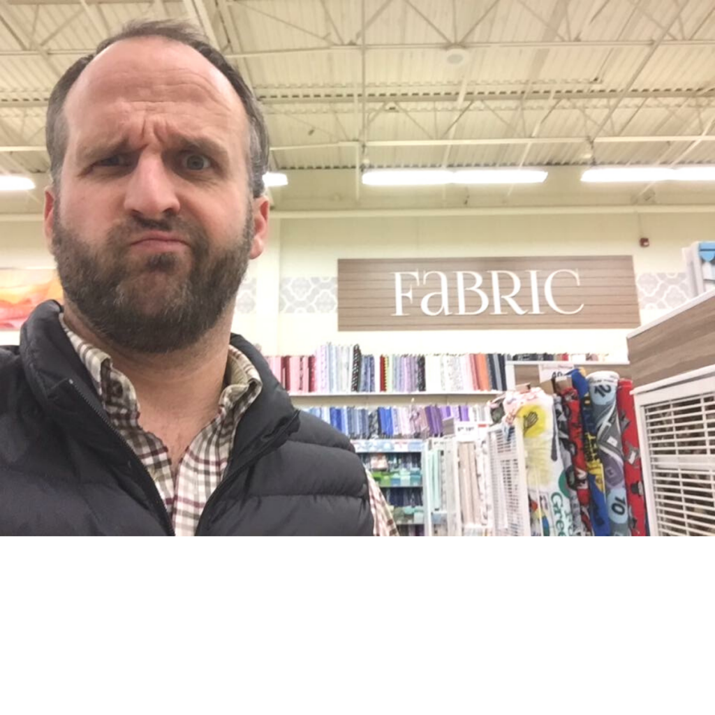 """A guy with a beard staring at the camera with a funny grin on his face. He's standing in front of a large sign on a store wall that reads, """"fabric"""" in big bold letters."""