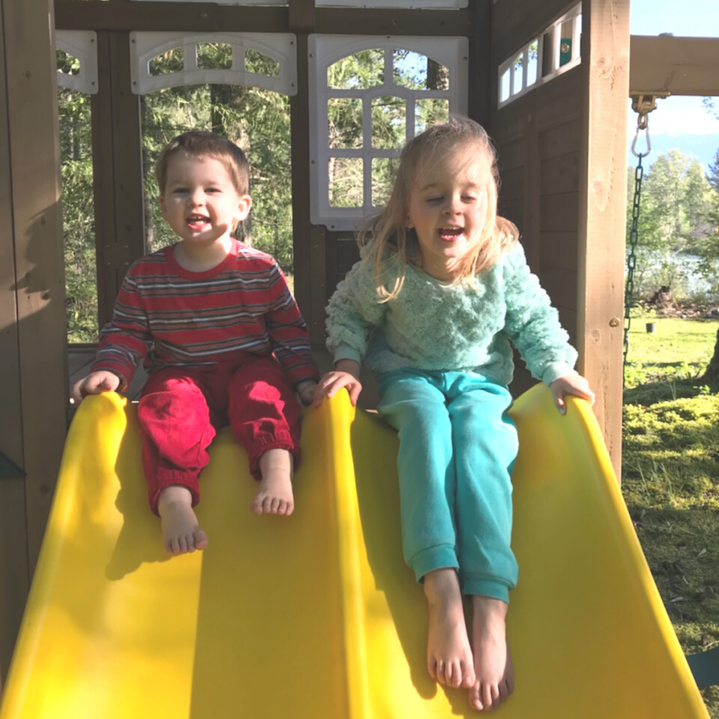 two kids sitting on the yellow slide of a playlet. One little girl and one little boy. both smiling and getting ready to zoom down the slide towards mom who's taking the picture