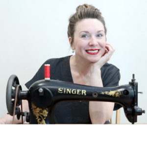 A girl wearing a black linen top and bright red lipstick. She has her hair loosely pulled up into a bun and is smiling at the camera sitting behind her vintage singer treadle sewing machine