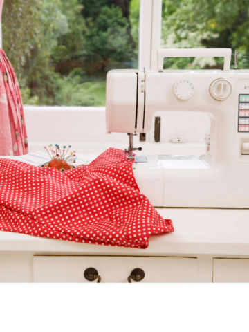 a white sewing machine sitting on a sewing table draped to the side with some beautiful red fabric. A red dress is on a dress form in the background.