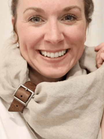 girl smiling at the camera wearing a simple oversized tan linen shawl with leather band accessory