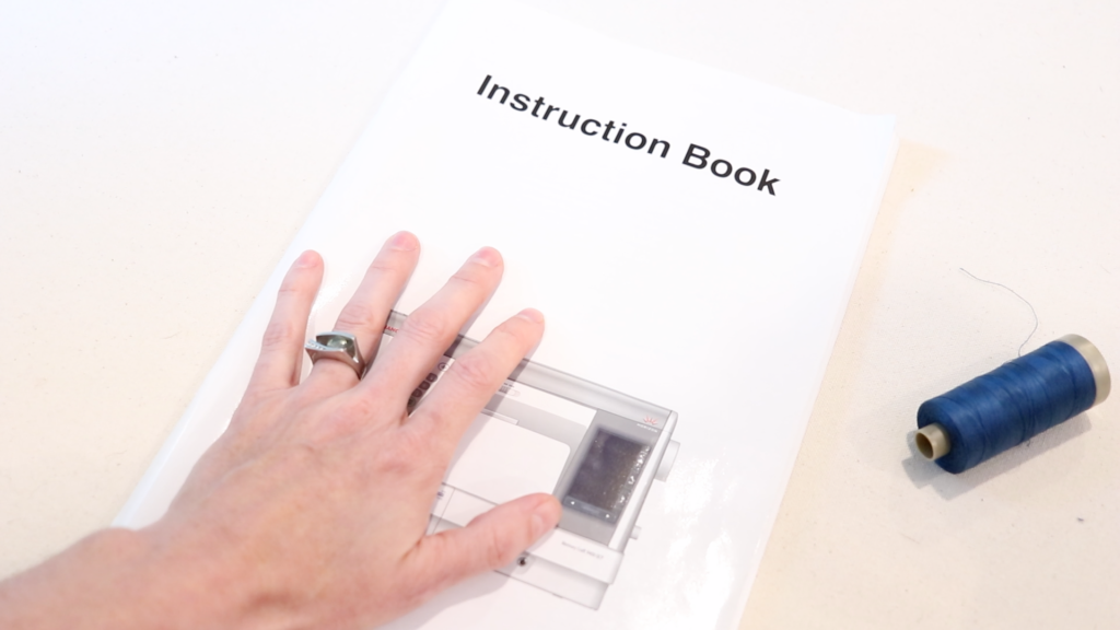 hand resting on a sewing machine instruction book